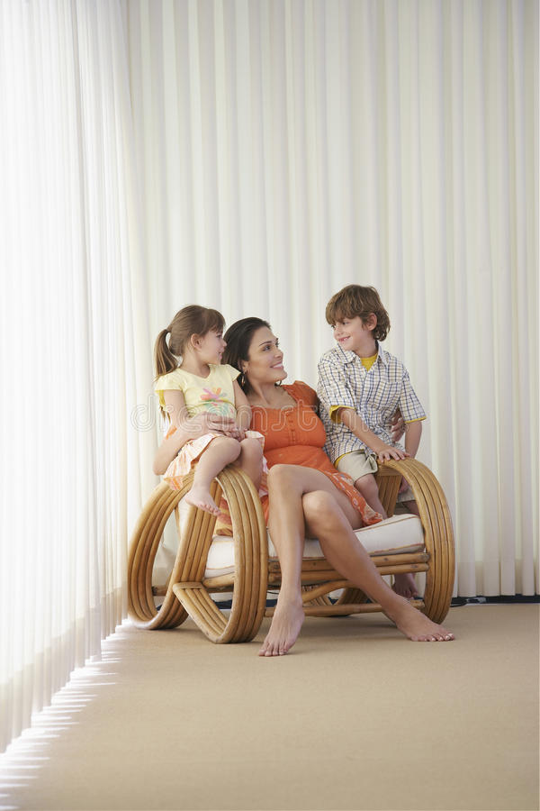 Mère avec des enfants s'asseyant sur le fauteuil images stock