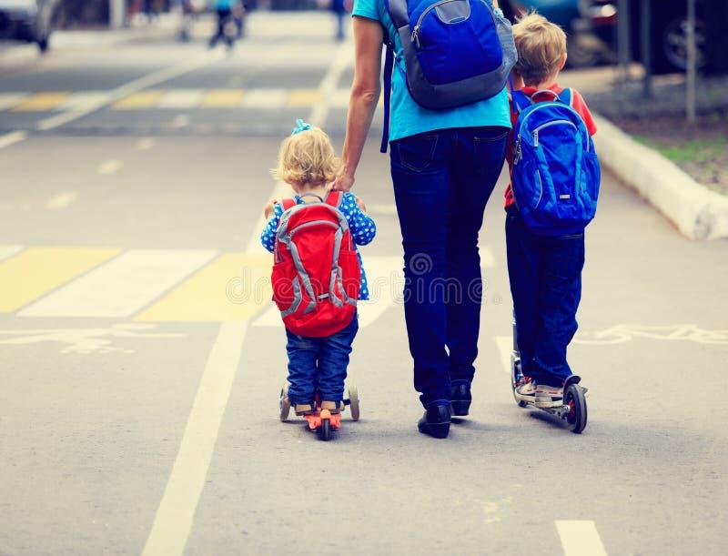 Mère avec des enfants sur des scooters montant le long de la route photos libres de droits