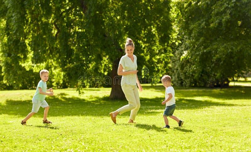 Mère avec des fils jouant le jeu de crochet au parc d'été image libre de droits