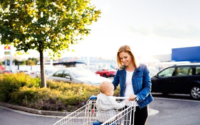 Mère avec l'achat allant de bébé garçon en parking images libres de droits