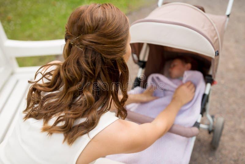 Mère avec l'enfant dans la poussette au parc d'été photos stock