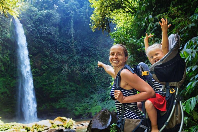 Mère avec l'enfant dans le sac à dos augmentant à la cascade de jungle image libre de droits