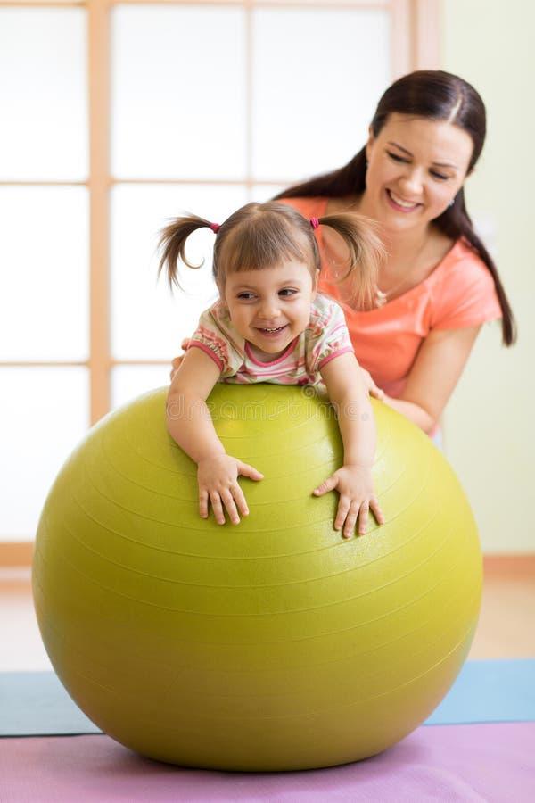 Mère avec l'enfant heureux faisant des exercices avec la boule gymnastique à la classe de forme physique Concept des soins de la  photos stock