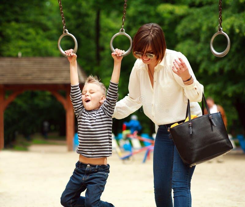 Mère avec l'enfant jouant sur l'oscillation sur le terrain de jeu d'été en parc photo stock
