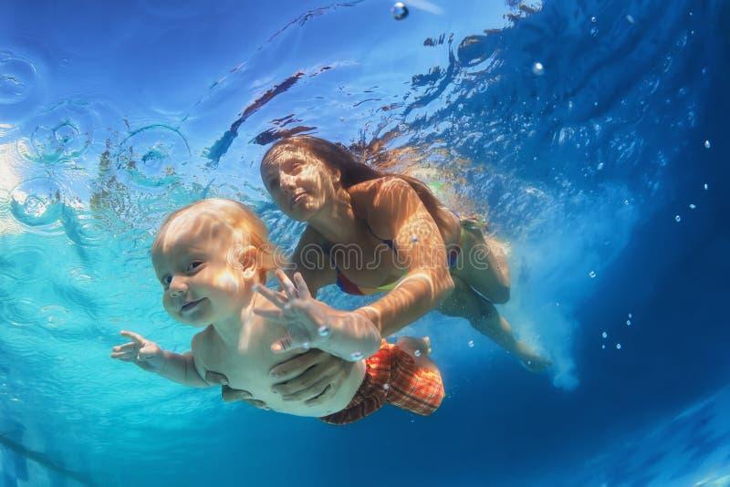 Mère avec l'enfant nageant sous l'eau dans la piscine photo stock