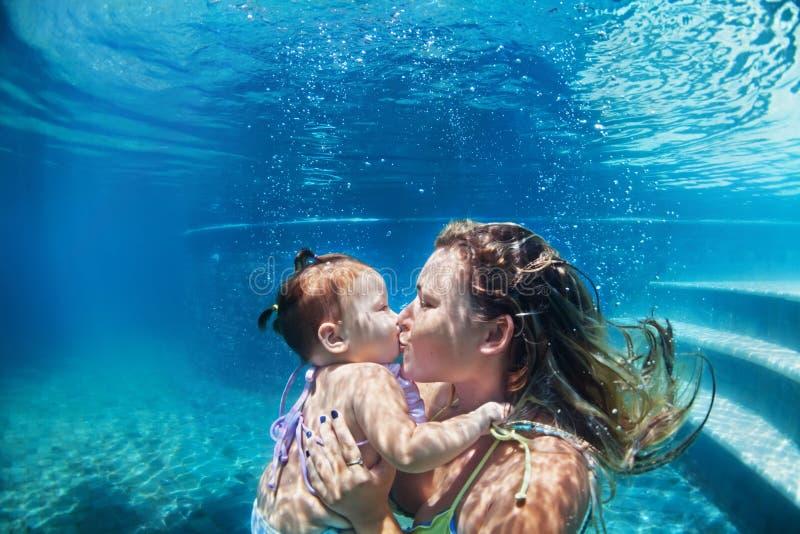 Mère avec l'enfant nageant sous l'eau dans la piscine bleue de plage photographie stock libre de droits