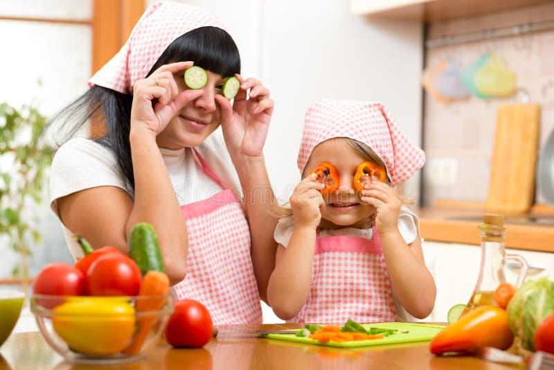 Mère avec l'enfant préparant la nourriture saine et ayant l'amusement photo stock