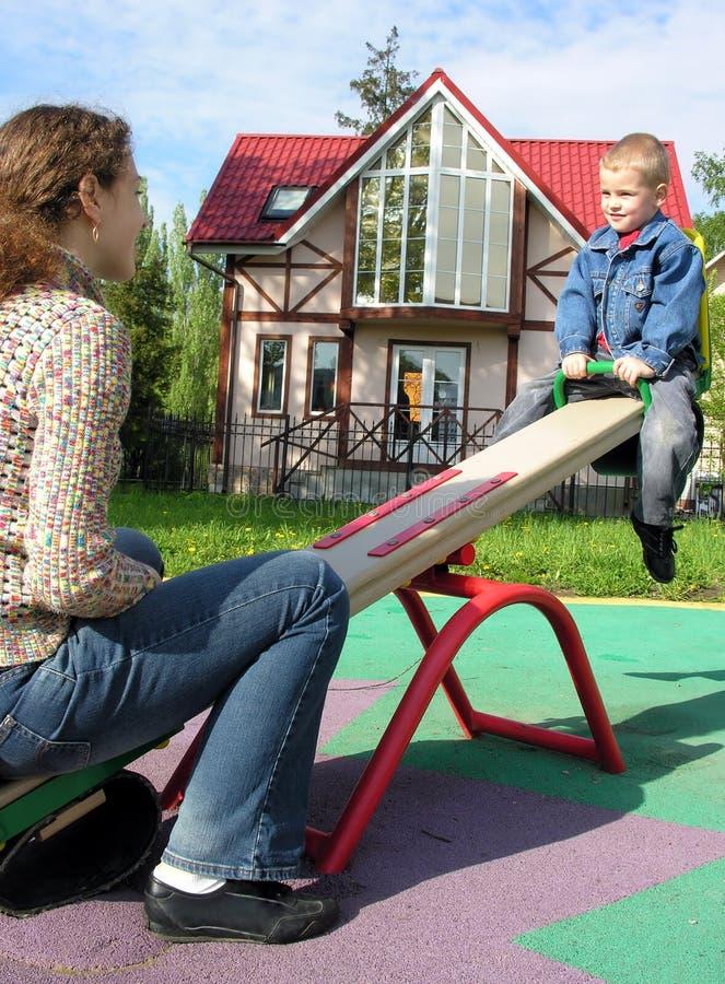 Mère avec l'enfant sur la balançoir photos stock