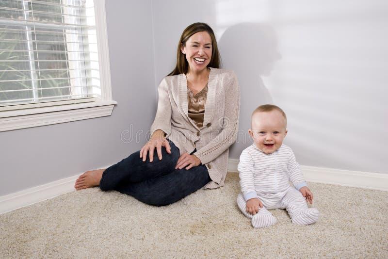 Mère avec la chéri heureuse s'asseyant sur le tapis photos stock