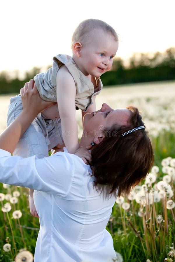 Mère avec la chéri jouant sur le pré photo stock