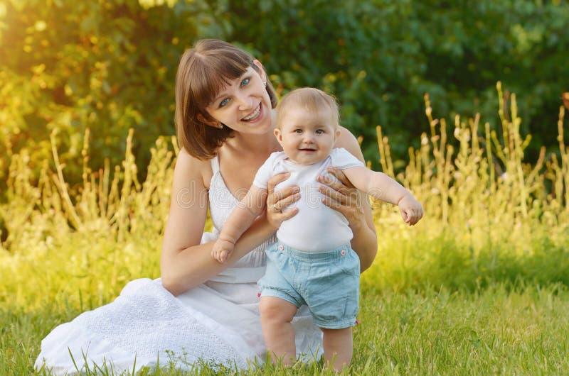 Mère avec la chéri sur l'herbe verte photo stock