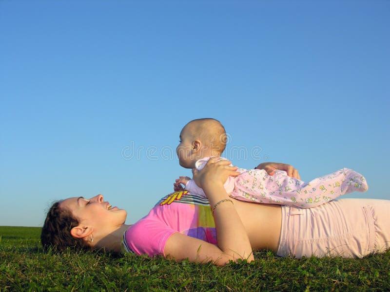 Mère avec la chéri sur le mensonge de coucher du soleil images stock