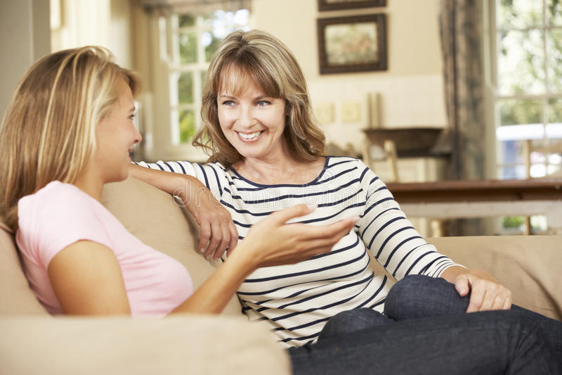 Mère avec la fille adolescente s'asseyant sur Sofa At Home Chatting photo stock
