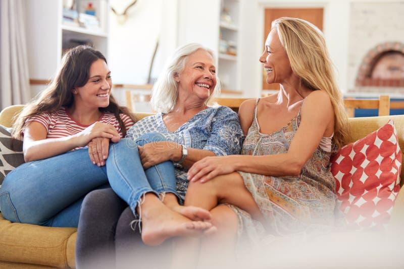 Mère avec la fille adulte et la petite-fille adolescente détendant sur Sofa And Talking At Home images libres de droits