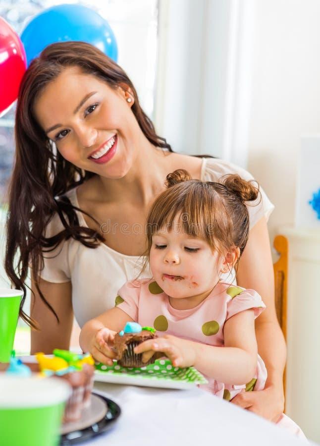 Mère avec la fille d'anniversaire à la maison image libre de droits