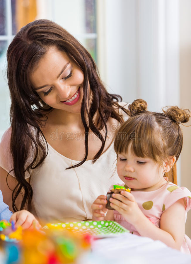 Mère avec la fille d'anniversaire mangeant le petit gâteau image libre de droits