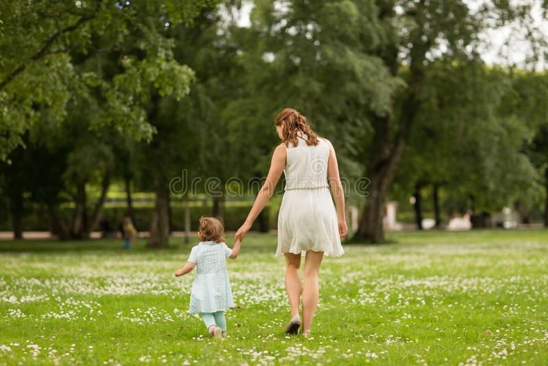Mère avec la fille de bébé marchant au parc d'été image libre de droits