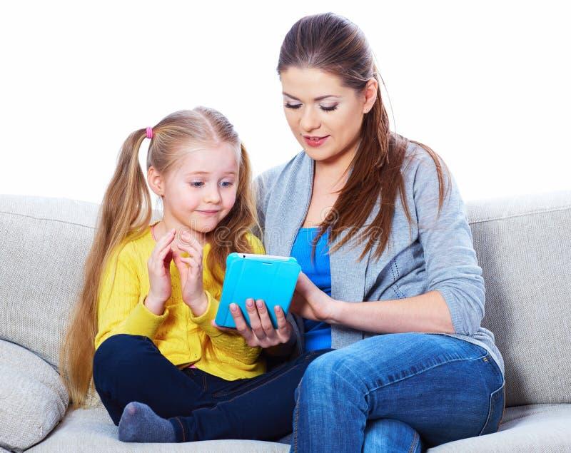 Mère avec la fille s'asseyant sur l'étude de travail de maison de sofa photographie stock libre de droits