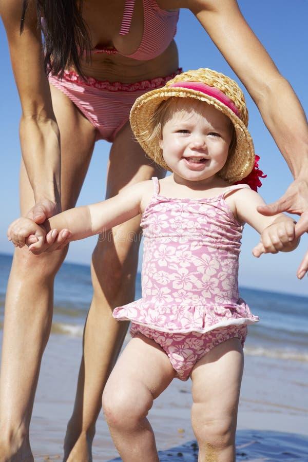 Mère avec la jeune fille marchant le long de la plage ensemble photographie stock