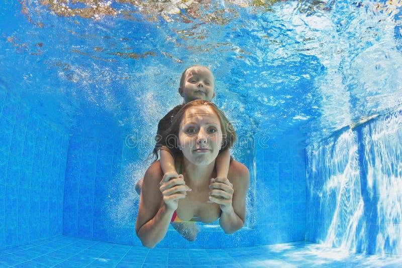 Mère avec la natation et la plongée d'enfant sous-marines dans la piscine photographie stock libre de droits