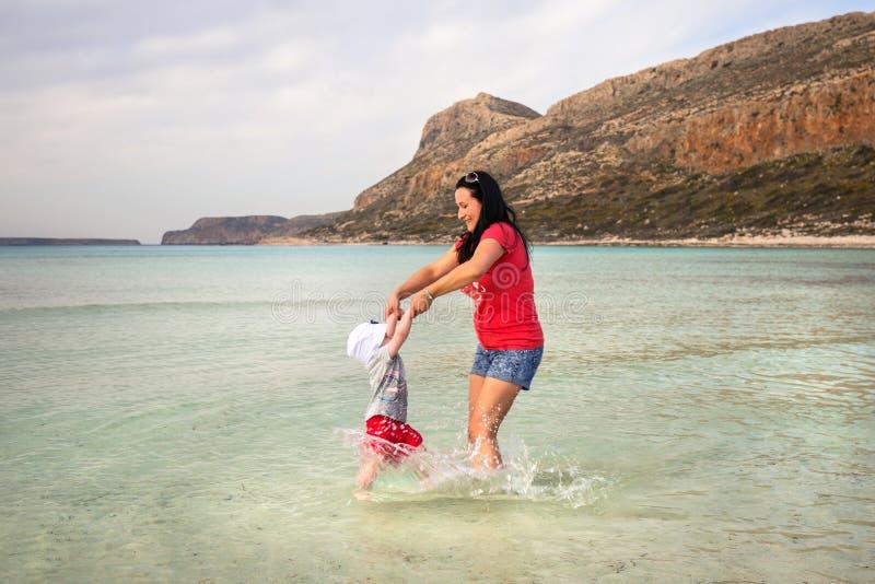 Mère avec la petite fille jouant dans l'eau de la plage de Balos photo libre de droits