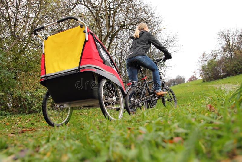 Mère avec la remorque de vélo d'enfant photo libre de droits