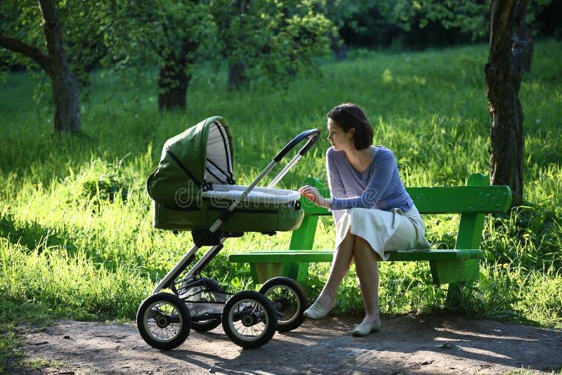 Mère avec la voiture d'enfant image stock