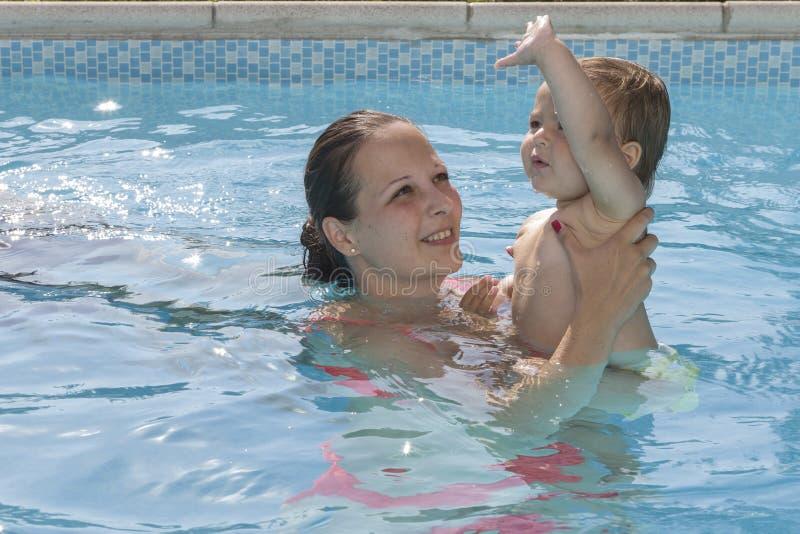 Mère avec le bébé appréciant une piscine image libre de droits
