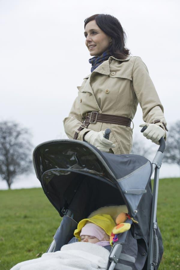 Mère avec le bébé dans la poussette au parc photo libre de droits