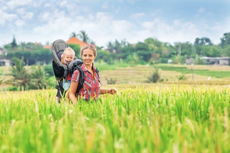 Mère avec le bébé dans le sac à dos de transport marchant sur des terrasses de riz photographie stock