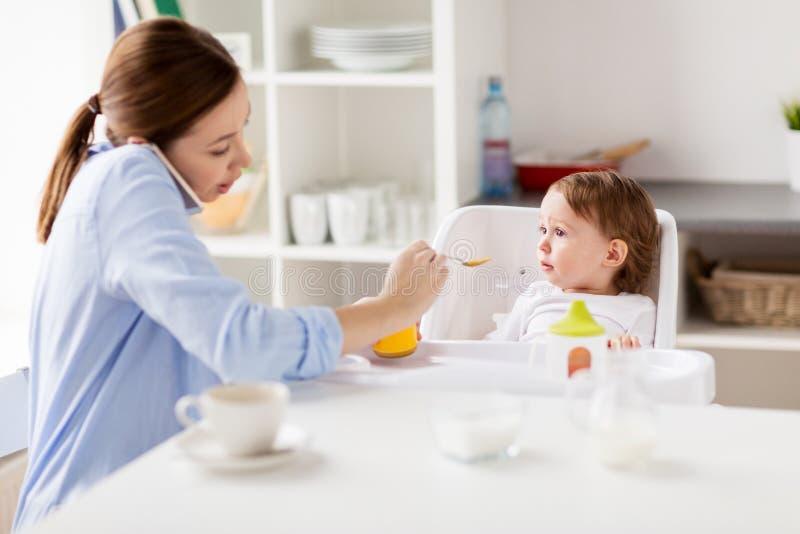 Mère avec le bébé de alimentation de smartphone à la maison photographie stock libre de droits