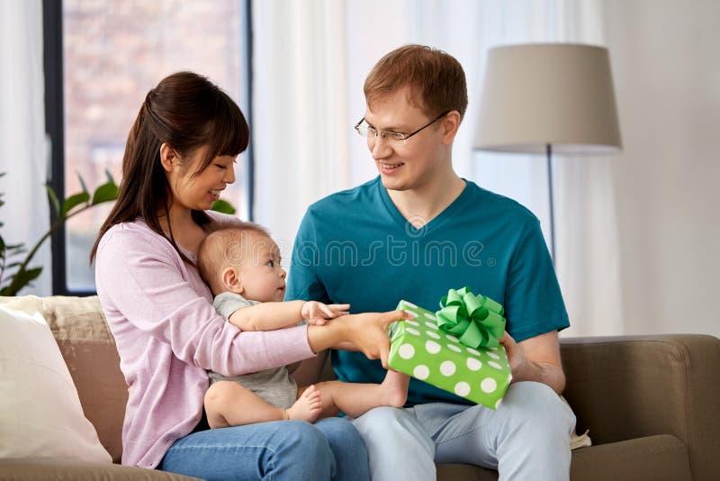 Mère avec le bébé donnant le cadeau d'anniversaire au père image libre de droits
