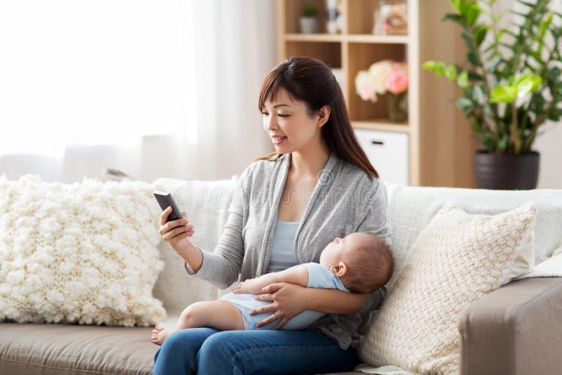 Mère avec le bébé et le smartphone de sommeil à la maison images stock