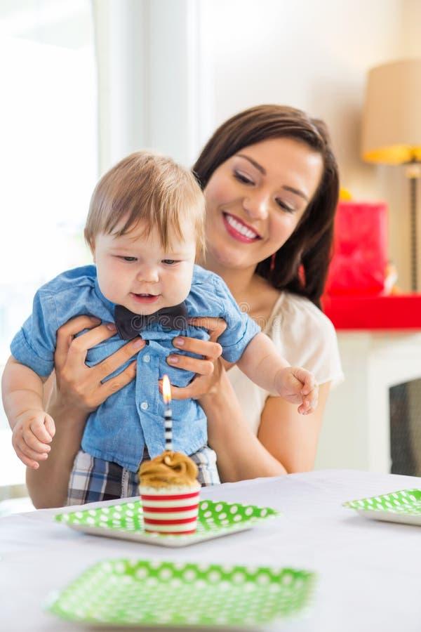 Mère avec le bébé garçon célébrant l'anniversaire à la maison photos stock