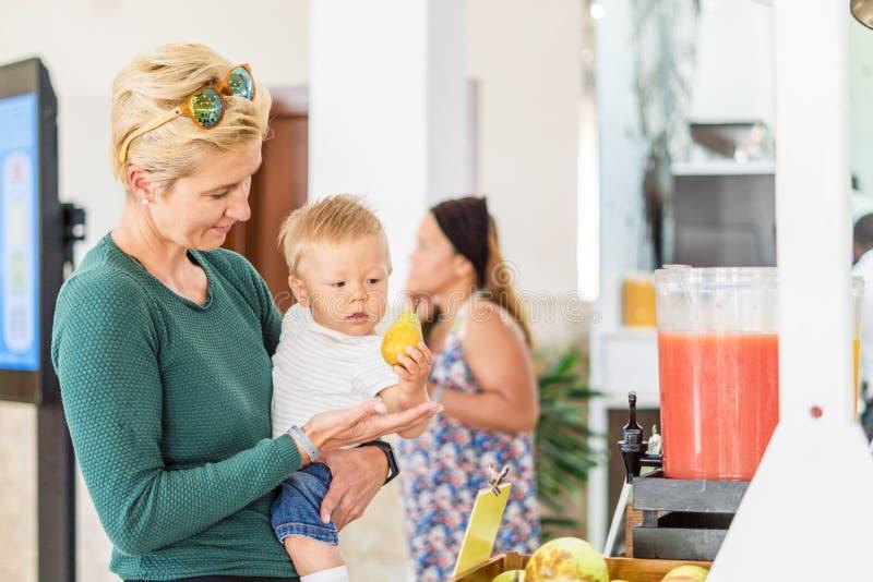 Mère avec le bébé garçon choisissant la poire dans tout le restaurant inclus image stock