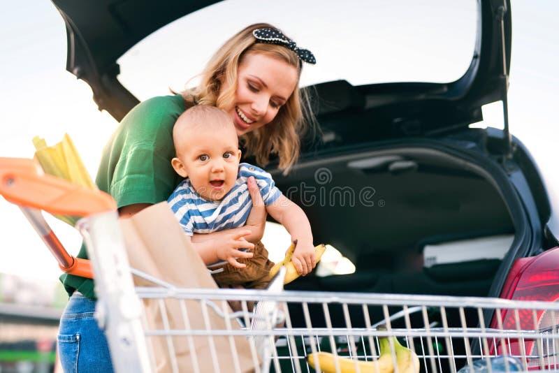 Mère avec le bébé garçon mettant des achats dans le dos de la voiture photo libre de droits