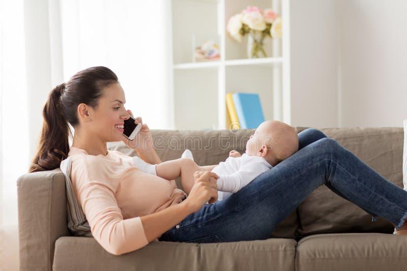 Mère avec le bébé invitant le smartphone à la maison photo stock