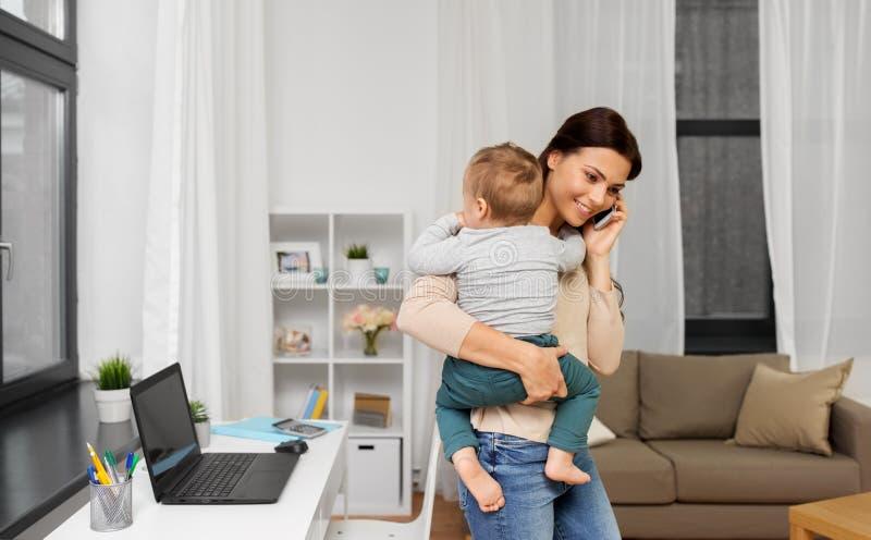 Mère avec le bébé invitant le smartphone à la maison photos stock