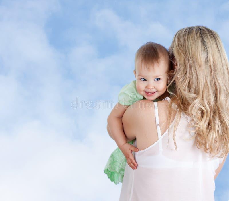 Mère avec le bébé mignon regardant au-dessus de l'épaule photo stock