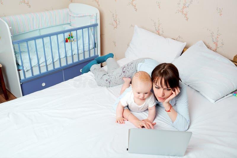 Mère avec le bébé sur le lit regardant un ordinateur portable avec enthousiasme photo stock
