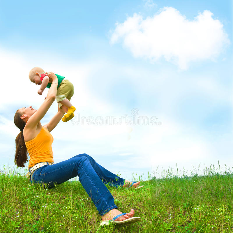 Mère avec le bébé sur le pré photo stock