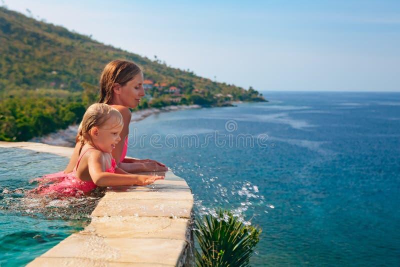 Mère avec le bain d'enfant avec l'amusement dans la piscine d'infini image libre de droits