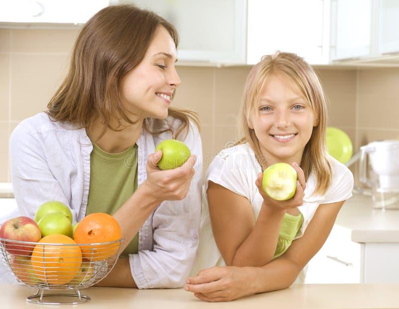 Mère avec le descendant mangeant des pommes photo stock