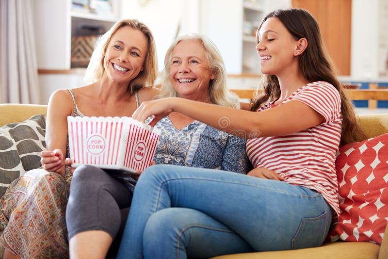 Mère avec le film de observation de fille adulte et de maïs éclaté adolescent de consommation de petite-fille sur Sofa At Home photos stock