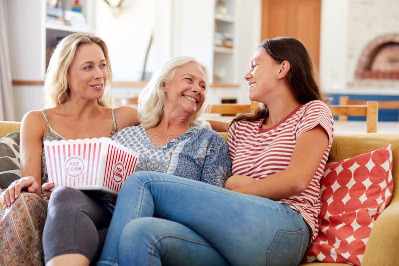 Mère avec le film de observation de fille adulte et de maïs éclaté adolescent de consommation de petite-fille sur Sofa At Home photographie stock libre de droits