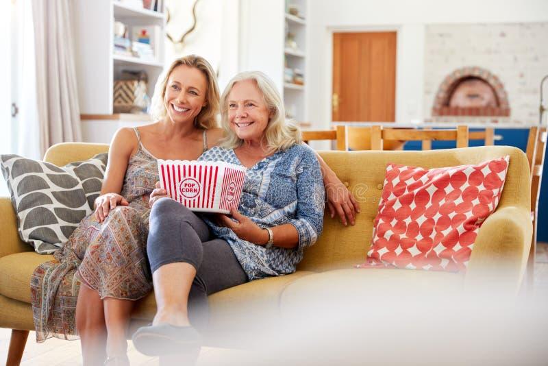 Mère avec le film de observation de fille de maïs éclaté adulte de consommation sur Sofa At Home Together photos stock