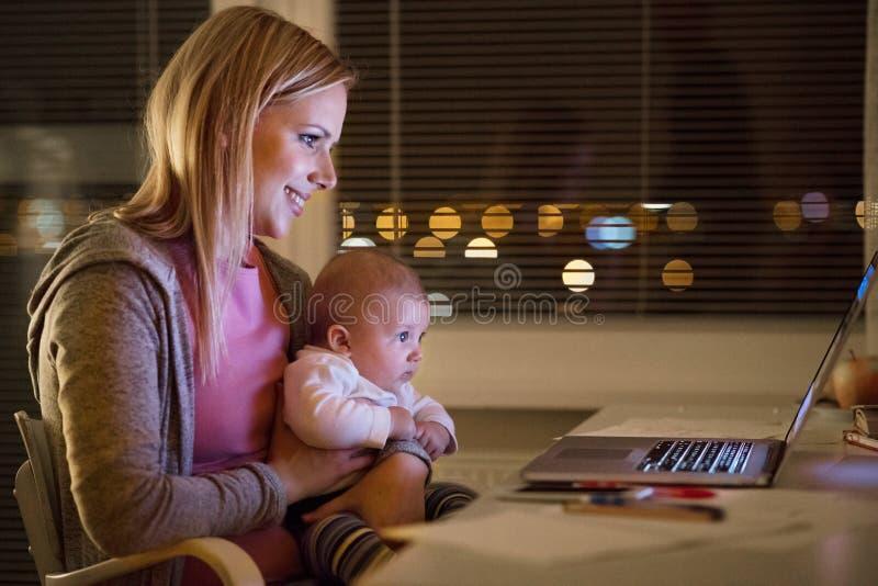 Mère avec le fils dans les bras, travaillant sur l'ordinateur portable images libres de droits