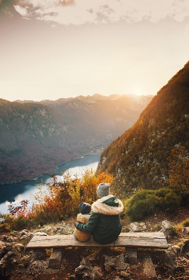Mère avec le fils regardant le coucher du soleil en montagnes images libres de droits