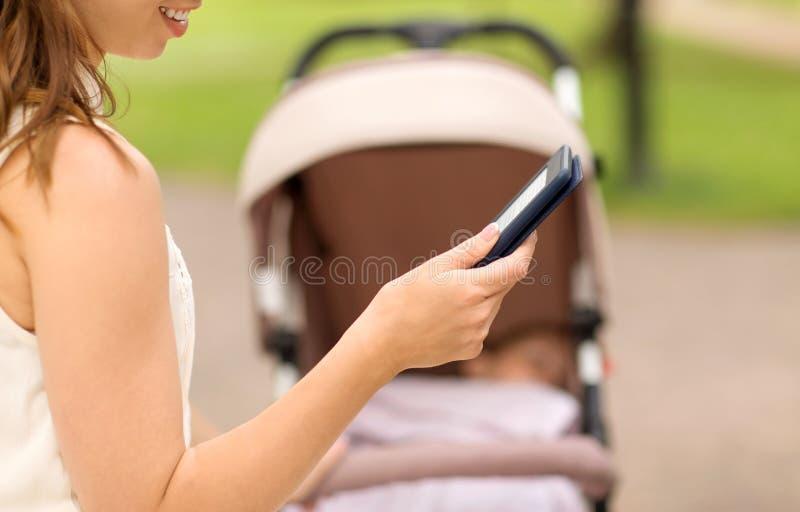 Mère avec le livre d'Internet de lecture de poussette au parc photo libre de droits