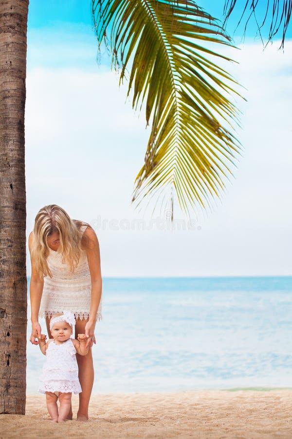 Mère avec le petit bébé mignon marchant près de la paume à la plage images libres de droits